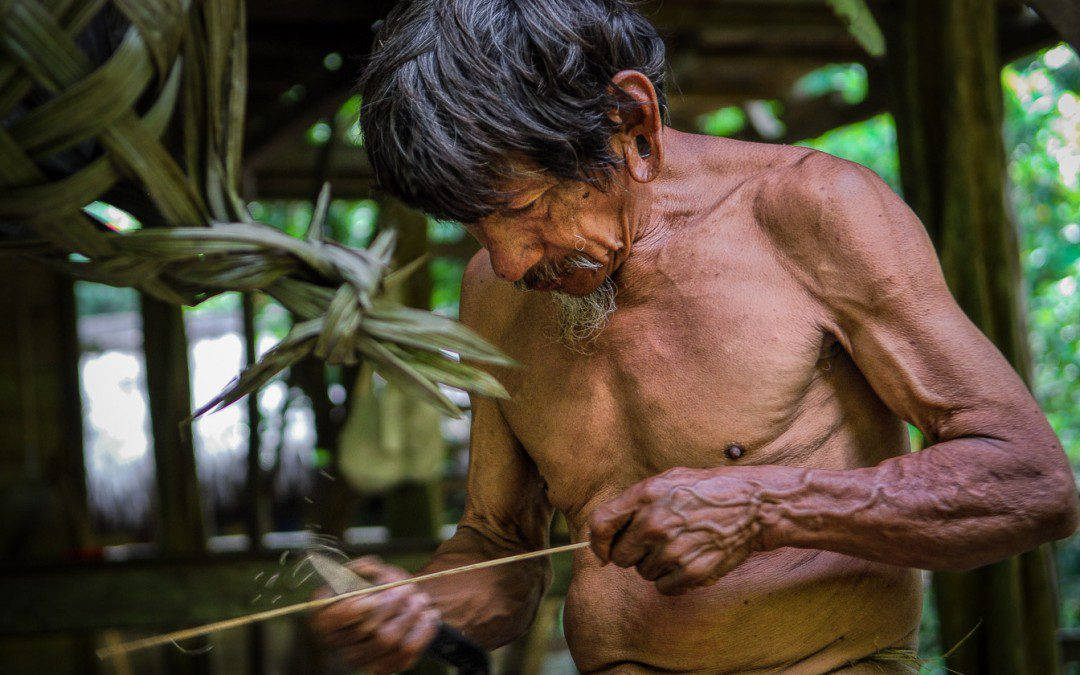 Huaorani Indian preparing arrows