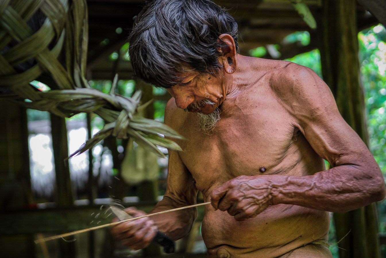 Huaorani Indian preparing arrows for his blowpipe
