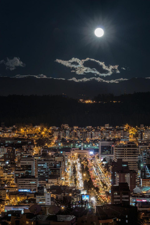 Blue moon rises over the Naciones Unidas avenue in Quito