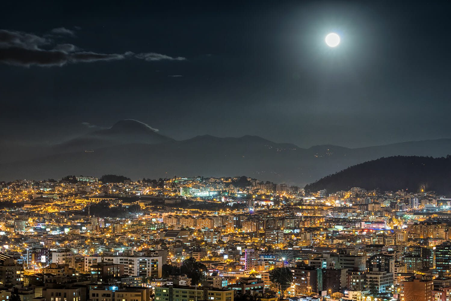 The full moon lights up the Cayambe volcano and north of Quito