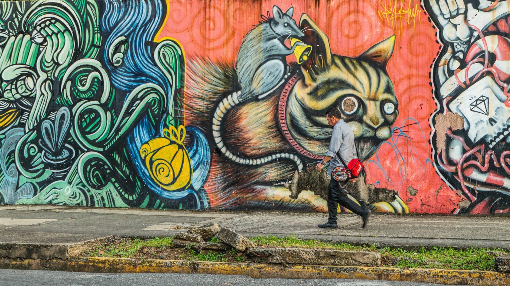 Man walking next to a wall of graffiti in San José Costa Rica