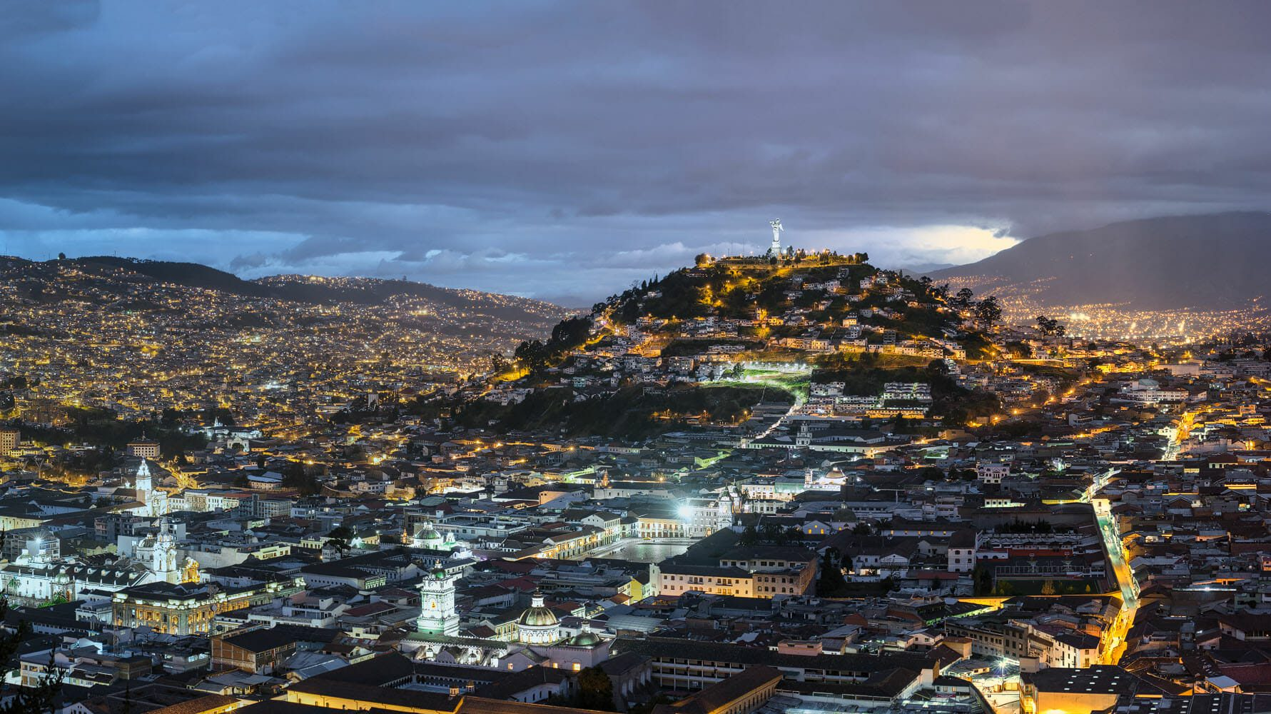 Panorama of the old town of Quito at blue hour dominated by the Panecillo and the Virgen de Quito statue